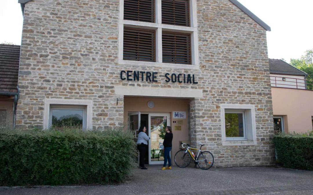 Des gens discutent devant l'entrée du centre social de Pouilly-en-Auxois