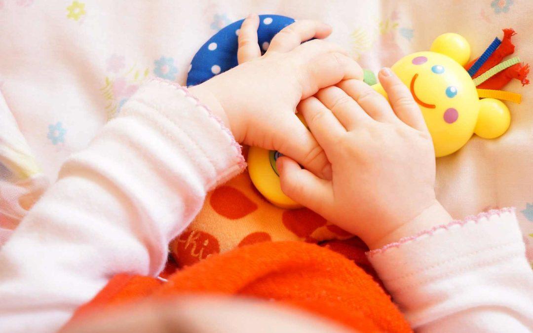Bébéqui joue avec un hochet